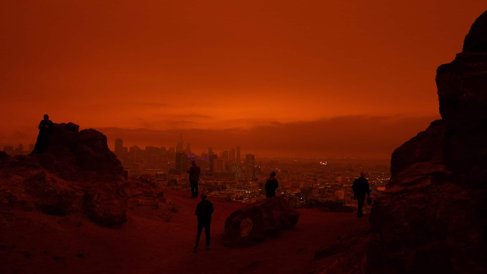 People on a hill watching raging wild fires close to a city