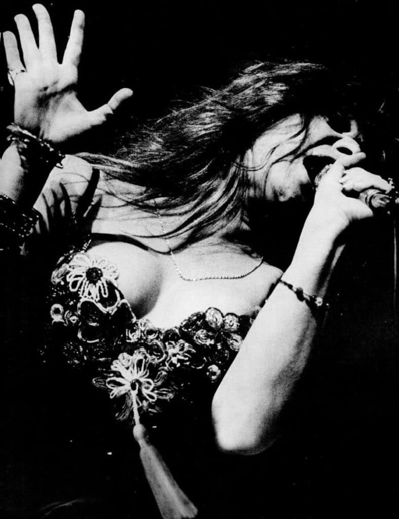 Black and white upper body shot of Janis Joplin performing on stage: wearing a top with an ornamental bead flower design, microphone in left hand, open palm of right hand in shoulder height, posture slightly leant towards the right border of the photo giving an impression of dynamic movement.